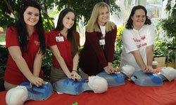 Image: Take Heart First Coast volunteers demonstrate hands-only CPR during the UF Health Jacksonville Wellness Fair.