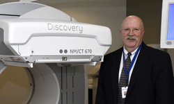 Image: Barry McCook, MD, associate professor and chair of radiology at the University of Florida College of Medicine – Jacksonville, stands beside a PET-CT scanner, one of several new imaging devices at UF Health North.