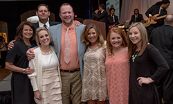 Image: Mark Taylor, in the paisley necktie, is surrounded by family and friends during the Feb. 6 A Night for Heroes gala, which benefited TramaOne at UF Health Jacksonville. Mark was recognized for his perseverance and strength, as he