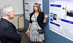 Image: Emergency medicine resident Alexandra Mannix, MD, discusses her poster display for Advances in Medical Education, which proceeded the graduation ceremony. Jeffrey House, DO, an associate professor of medicine and director of the internal medicine residency program, looks on.