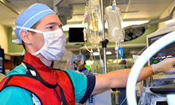 Image: Chris Schwan, MD, a second-year anesthesiology resident physician at the University of Florida College of Medicine – Jacksonville, manages anesthesia during a pulmonary vein isolation.
