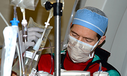 Image: Schwan adjusts a fluid bag during the procedure, which was to correct an abnormal heart rhythm.