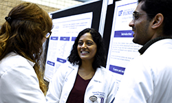 Image: Internal medicine resident physicians, from left, Trisha Shelley, DO; Ashley Thomas, MD; and Satish Maharaj, MD, converse while viewing some of the posters on display during Celebration of Research.