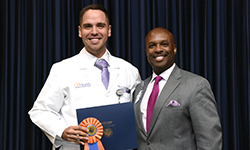 Image: Jose Rivas Rios, MD, accepts the first-place poster presentation award on behalf of Dmitry Yaranov, MD. Both are internal medicine resident physicians. Rivas Rios was a coauthor on the study.