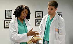 Image: Abimbola confers with orthopaedic surgery resident Zachary Elstad, MD, before an early-morning didactic session.