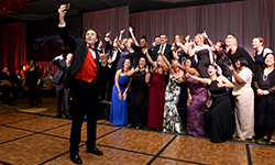 """Image: Chris Hemmen takes an enthusiastic selfie during the """"A Night for Heroes"""" gala, with many of his UF Health caregivers in the background."""