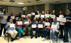 Image: Salman, seated third from right, is joined by other medical professionals, who are displaying papers representing their home countries.