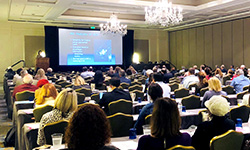 Image: The audience looks on as Susan Weinstein, MD, discusses imaging of ductal carcinoma in situ. Weinstein was one of several presenters during the multiday symposium, which drew world-renowned physicians and researchers to Amelia Island in February.