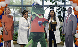 Image: Cardiovascular disease fellow Khadeeja Esmail, MD, winner of the Edward Jelks Outstanding Resident Clinician Award, displays her accolade alongside fellowship program director Gladys Velarde, MD, and life-like cut-off versions of Linda Edwards, MD, Albert E. Gator and Leon L. Haley Jr., MD, MHSA.