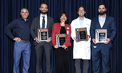Image: Four of the award winners display their plaques during Wednesday's festivities. They are, from left, Aaron Richardson, MD, MS; Elisa Sottile, MD; Anthony Stack II, DO; and Barrett Attarha, DO.