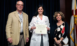 Image: Shands Jacksonville pharmacy resident Jocelyn Congdon, Pharm.D. (middle), is presented the Most Outstanding Poster Presentation by Resident Award by Daniel Wilson, M.D., Ph.D., dean of the UF College of Medicine-Jacksonville, and Elisa Zenni, M.D., associate dean for educational affairs