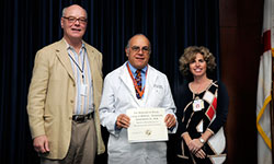 Image: Joseph Sabato Jr., M.D. (middle), a UF assistant professor of emergency medicine, is presented the Most Outstanding Poster Presentation by Faculty Award by Daniel Wilson, M.D., Ph.D., dean of the UF College of Medicine-Jacksonville, and Elisa Zenni, M.D., associate dean for educational affairs